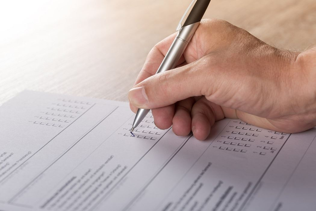 A hand holds a pen to take a written survey